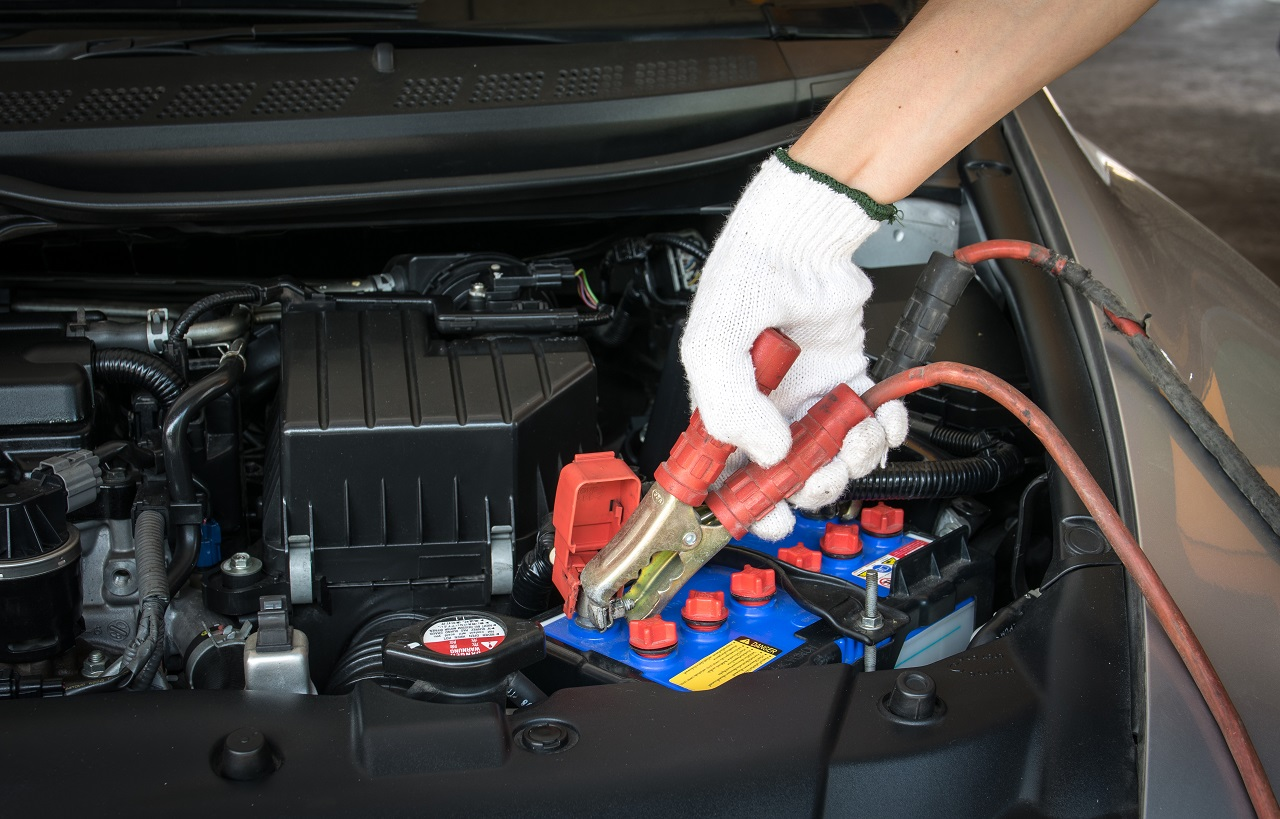 Automotive technician performing Car Jump Start Services on a dead car